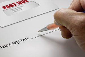 Pen in hand ready to sign a signature regarding a debt